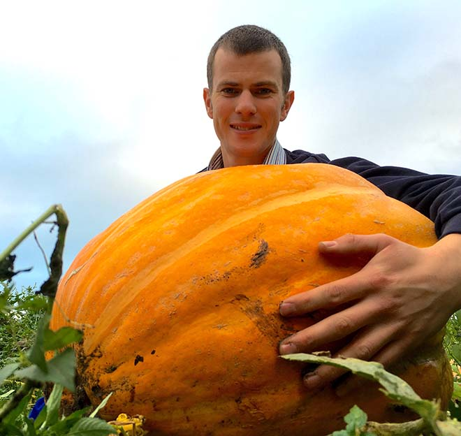 Rees Keene holding a big pumpkin at Over Farm